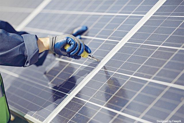 Operario arreglando un panel solar con una herramienta